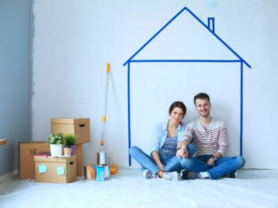 Couple sitting in front of wall in new unfinished home