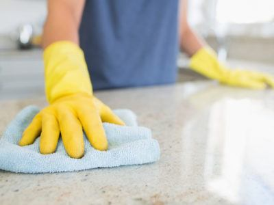 Woman cleaning stone counter top with a rag.