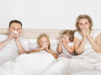 Sick parents with two sick children blowing their noses while laying in bed with a white comforter.