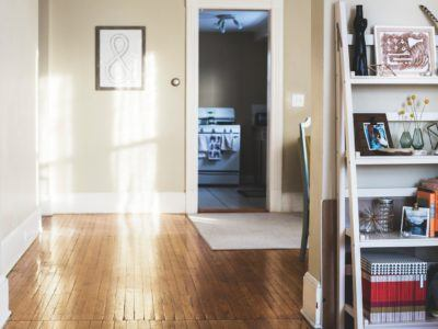 A clean and tidy living space with beige walls and wood floors.
