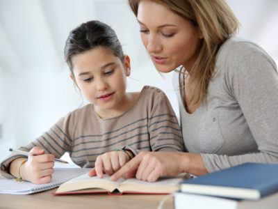 Mom helping kid with school homework at the table.