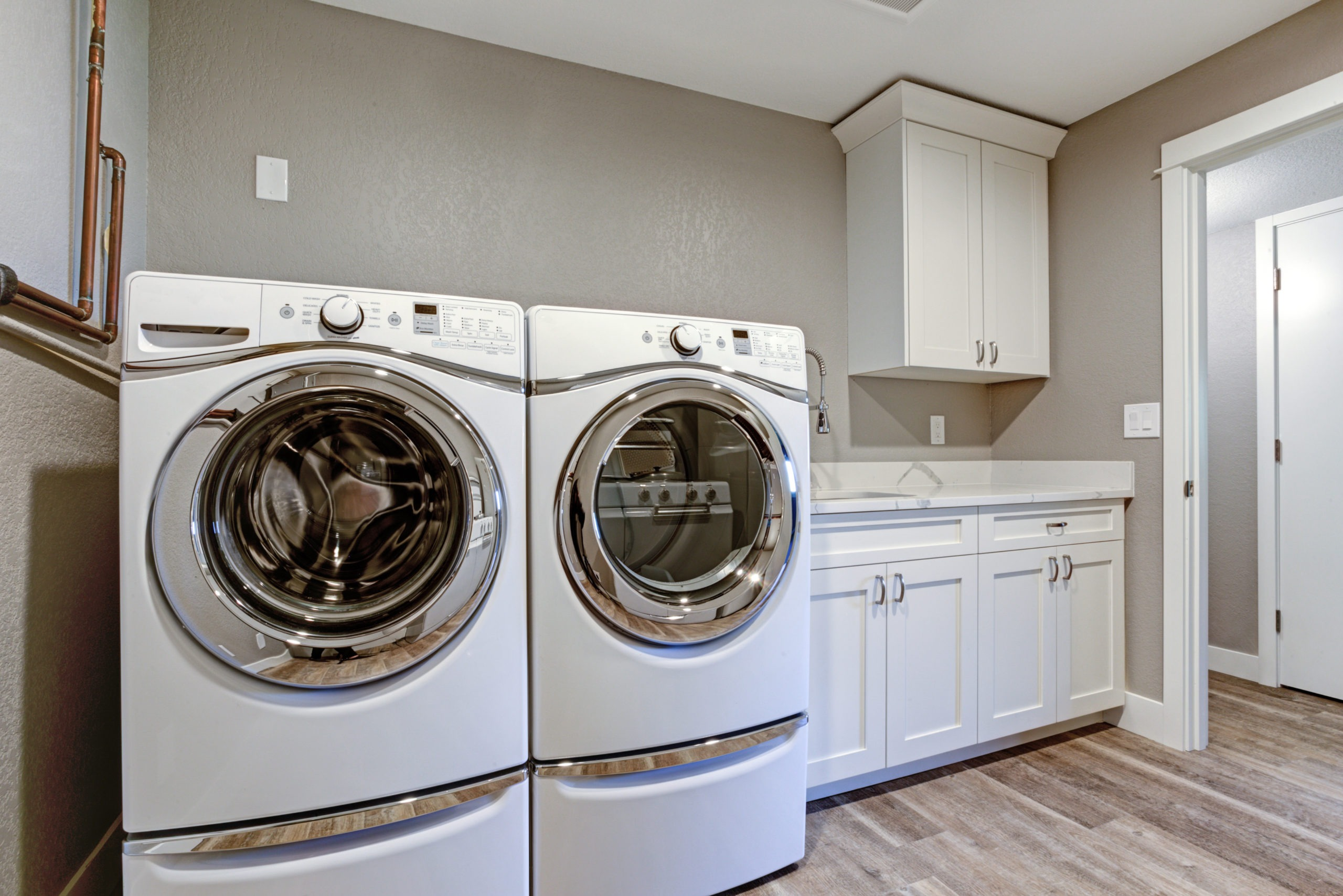 Laundry room with taupe walls and modern appliances.