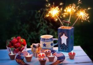 Festive 4th of July table setting outside including a bowl of strawberries, lit sparklers, and a decorative plate with lit candles.