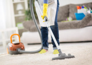 Cleaning service cleans carpet with vacuum cleaner