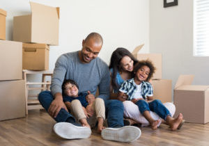A happy family of two boys and their parents sitting on the wood floor in their new home surrounded by cardboard moving boxes.