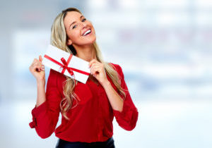 Happy woman wearing red holding an envelope tied with a red ribbon and bow.