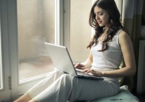 A brunette woman in white sitting in front of a window, using a laptop.
